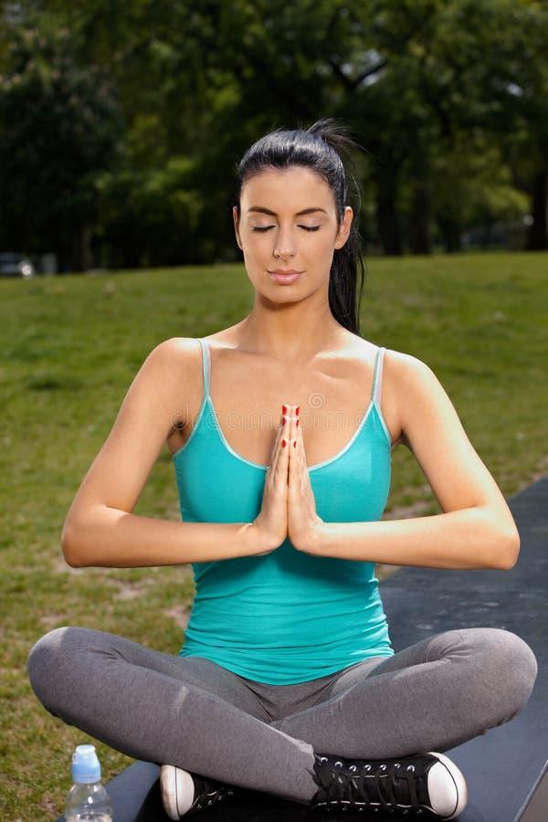 Yoga de pratique de joli femme en stationnement photos libres de droits