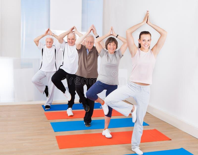 Yoga de pratique de personnes en position d'arbre au gymnase photos stock