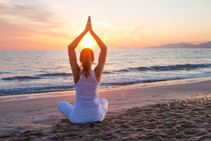 Yoga de pratique de femme caucasienne au bord de la mer images libres de droits