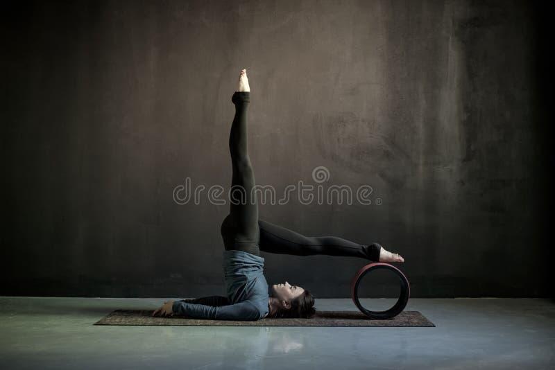 Yoga de pratique de femme, faisant l'exercice de Salamba Sarvangasana image libre de droits