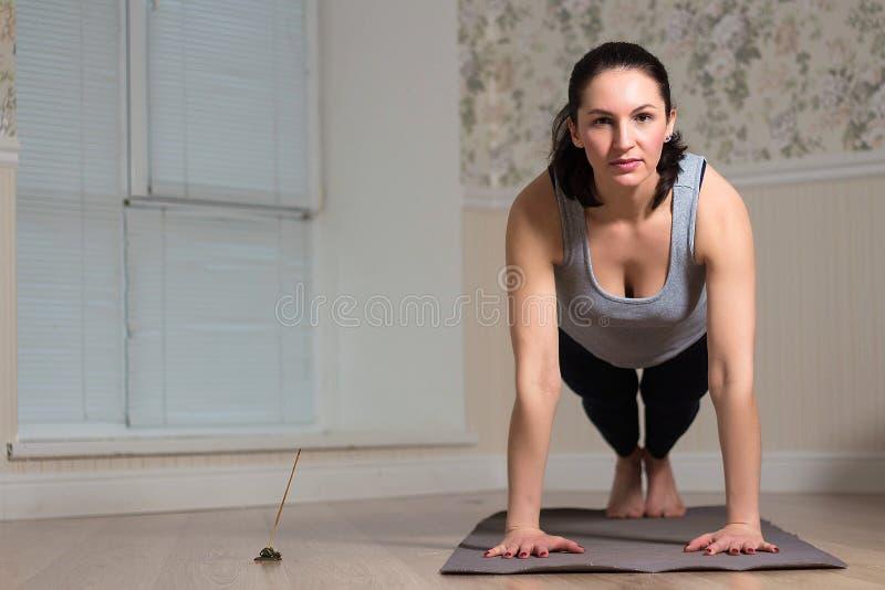 yoga de pratique de femme, pose de planche, vêtements de sport de port, intérieur de maison photos libres de droits
