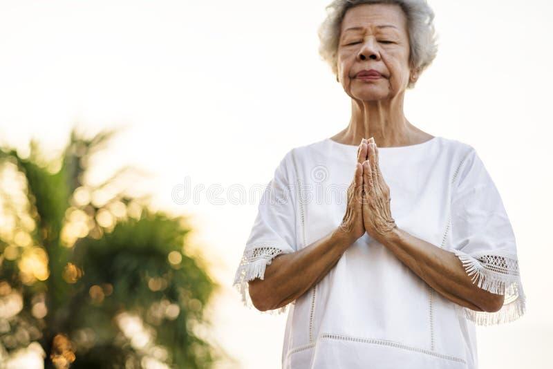 Yoga de pratique de femme supérieure pendant le matin image stock