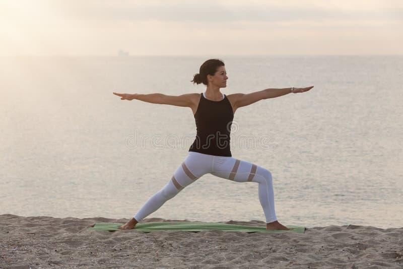 Yoga de pratique de femme sur la plage Pose de Worrior 2, Virabhandrasana II Dehors sports Vie saine photo libre de droits
