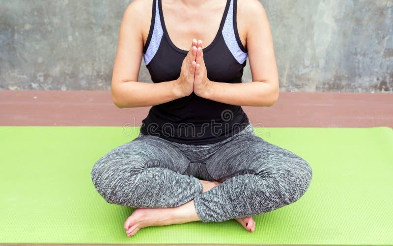 yoga de pratique de femme sur le tapis vert à l'arrière-plan d'urbain/mur photo libre de droits