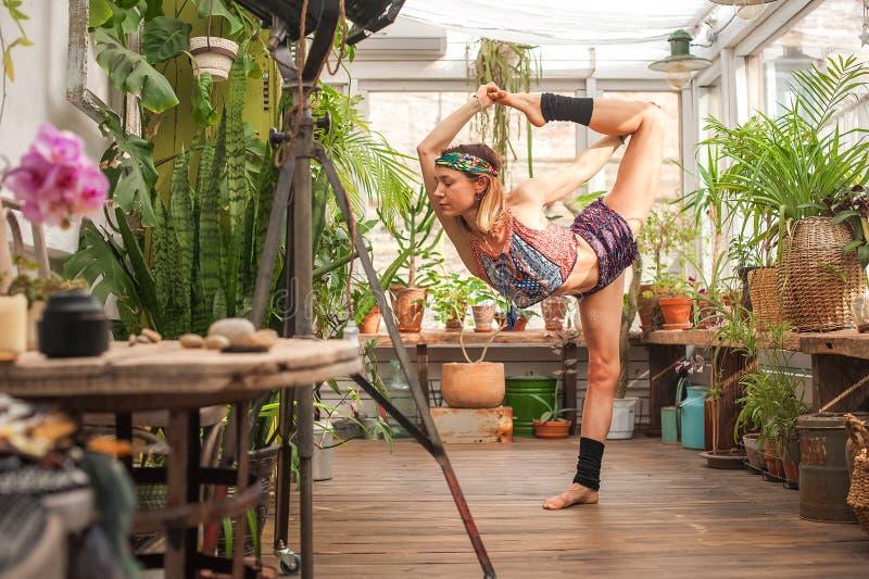 Yoga de pratique de fille sur la v?randa avec les fleurs ?troitement et l'espace de copie Femme dans des asanas de yoga en serre  image libre de droits