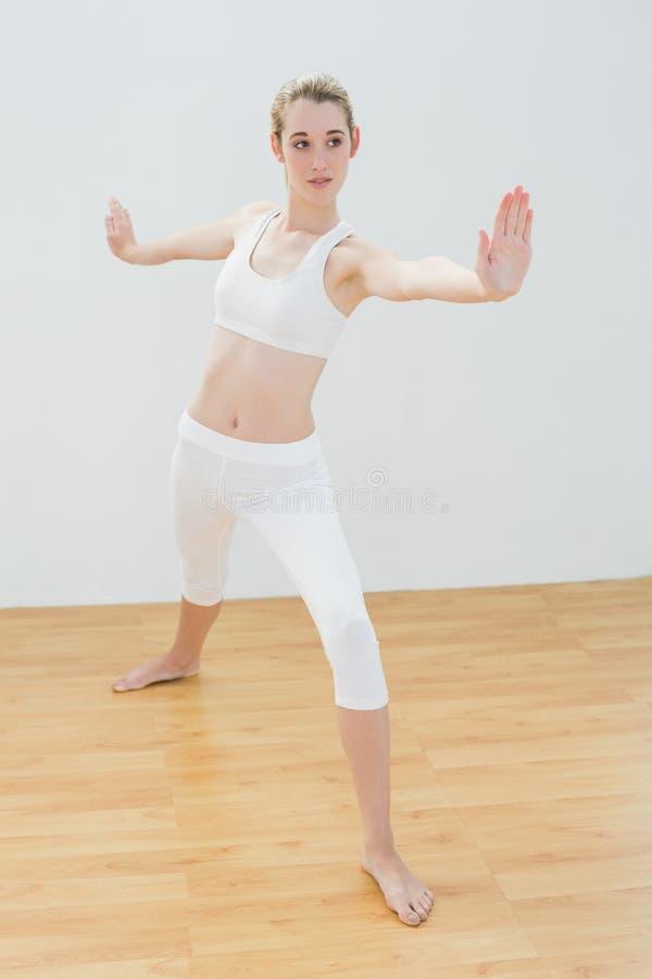 Yoga de pratique focalisé de femme convenable se tenant dans la salle de gymnastique photos libres de droits
