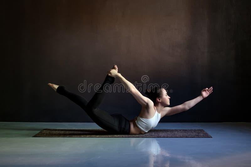 Yoga de pratique de jeune femme attirante, s'étendant dans la pose de Salabhasana images libres de droits