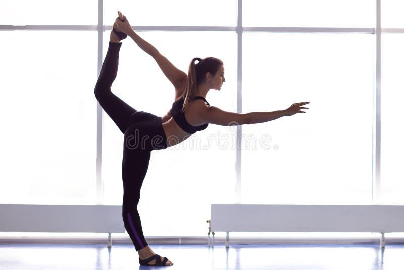 Yoga de pratique de jeune femme attirante, se tenant dans Natarajasana photos stock