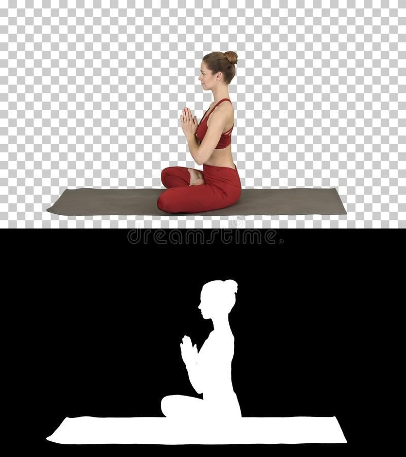 Yoga de pratique de jeune femme attirante sportive, faisant la pose de Lotus, Alpha Channel images stock