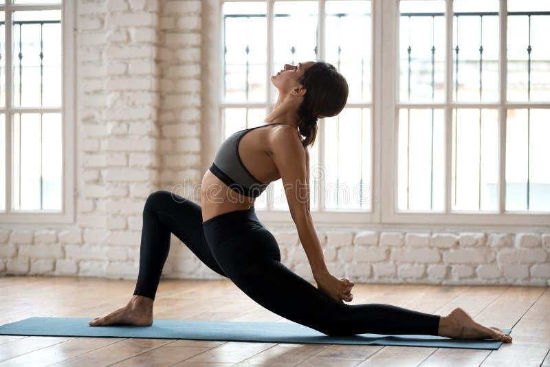 Yoga de pratique de jeune femme attirante de yogi, pose de cavalier de cheval photographie stock libre de droits