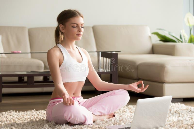 Yoga de pratique de jeune femme avec l'ordinateur portable, seul méditant au hom photos stock