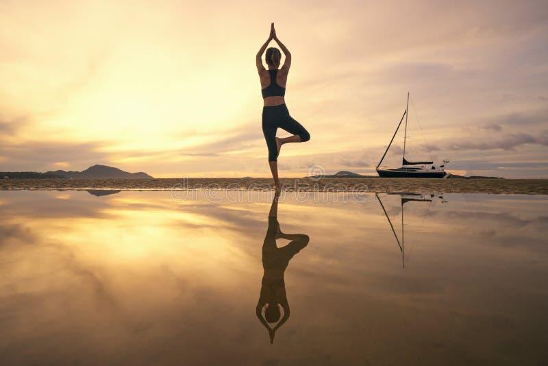 Yoga de pratique de jeune femme dans la nature, bonheur femelle, silhouette de yoga de pratique de jeune femme sur la plage au co photos libres de droits