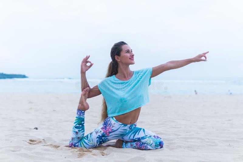 Yoga de pratique de jeune femme en bonne santé sur la plage au coucher du soleil photographie stock libre de droits