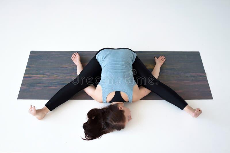 Yoga de pratique de jeune femme, faisant Kurmasana, posture de tortue, pose de tortue photo libre de droits