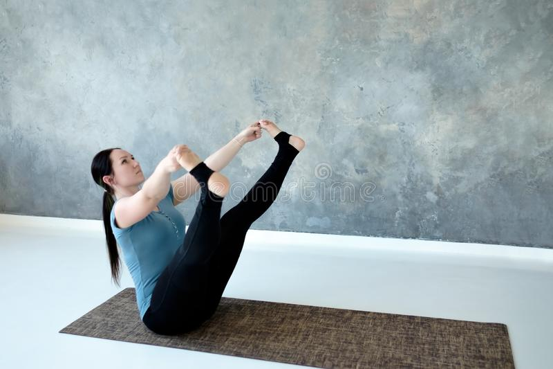 Yoga de pratique de jeune femme, faisant l'exercice à jambes large de bateau, Prasarita Navasana image libre de droits