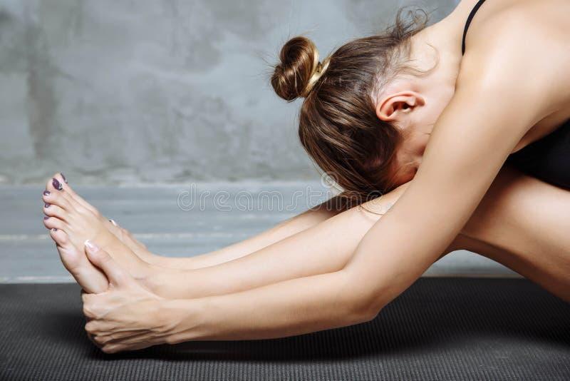 Yoga de pratique de jeune femme, se reposant dans l'exercice en avant posé de courbure, pose de paschimottanasana, établissant, v photos libres de droits