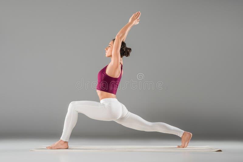 Yoga de pratique de jeune femme, se tenant dans l'exercice du guerrier un, Virabhadrasana photos stock