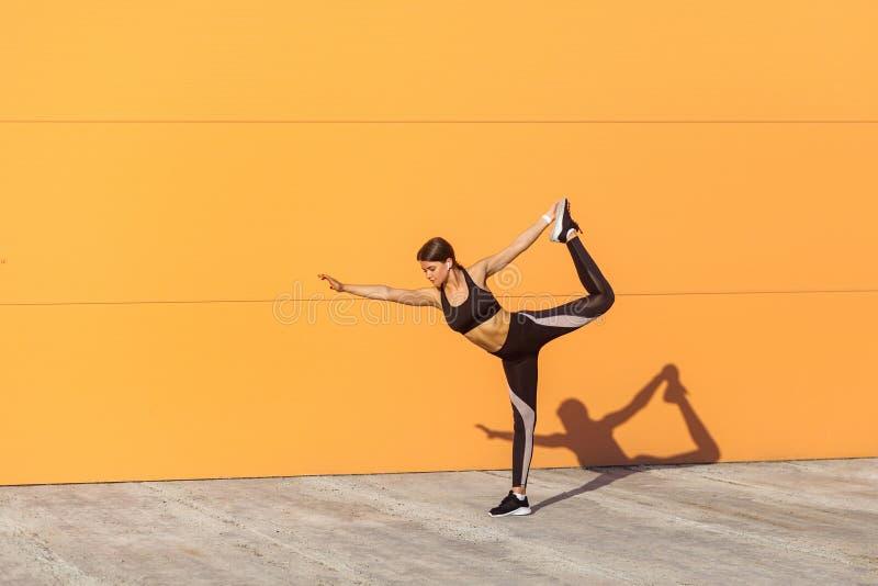 Yoga de pratique de jeune fille attirante, se tenant dans l'exercice de natarajasana, tenant l'équilibre, établissant, vêtements  image libre de droits