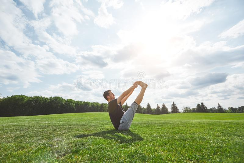 Yoga de pratique Jeune homme sportif s'étirant dehors sur une pelouse verte dans le domaine ouvert un matin ensoleillé Méditation images stock