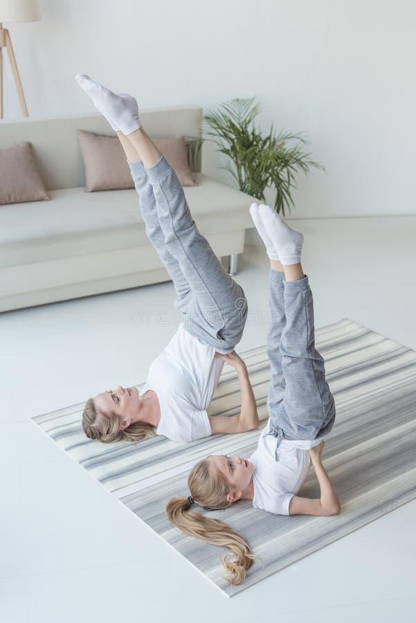 yoga de pratique de mère et de fille dans la pose soutenue de support d'épaule images libres de droits