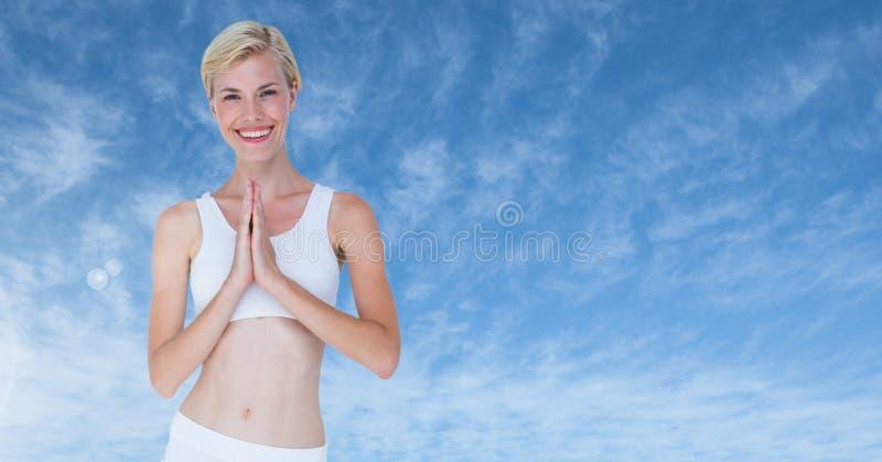 Yoga de rogación de la mujer que medita por las nubes azules imagenes de archivo