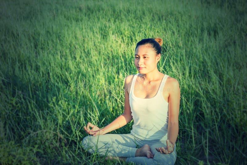 Yoga in de stad: de mooie jongelui past vrouw die sportkleding dragen die, ademhaling, zittend met gekruiste benen in Half Lotus  royalty-vrije stock foto's