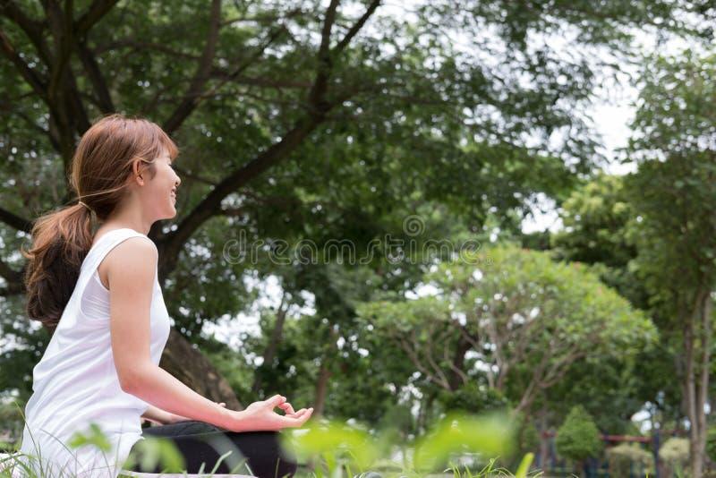 Yoga dehors en parc public La femme asiatique s'assied en position de lotus image stock