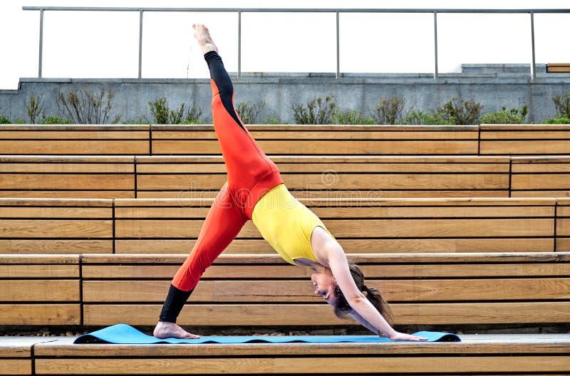 Yoga del ejercicio de la mujer joven en las manos de la ciudad para arriba y colocación de equilibrio en una pierna en día solead fotos de archivo libres de regalías
