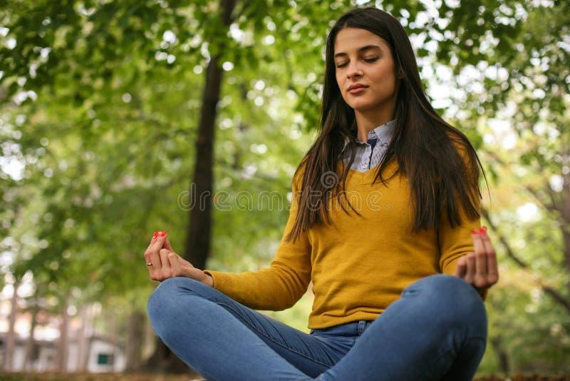 Yoga del ejercicio de la mujer joven en naturaleza imagenes de archivo