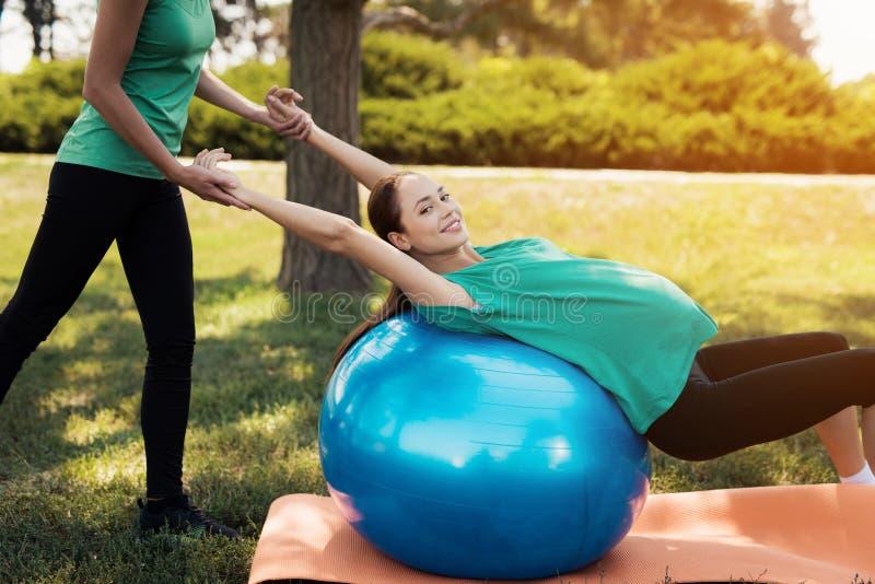Yoga del embarazo Una mujer está haciendo ejercicios en una bola azul para la yoga El coche le ayuda foto de archivo