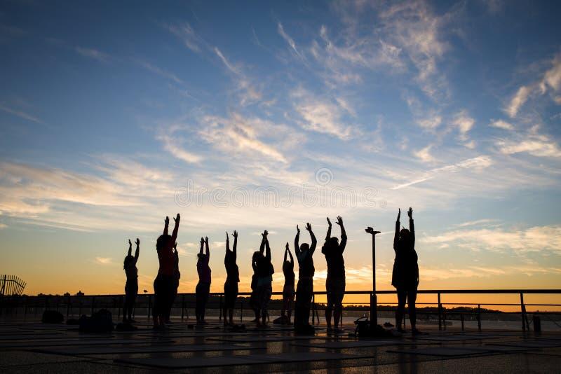 Yoga del gruppo ad alba fotografia stock