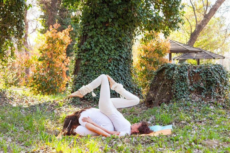 Yoga del socio de la pr?ctica del hombre joven y de la mujer al aire libre en el d?a de verano de madera fotografía de archivo