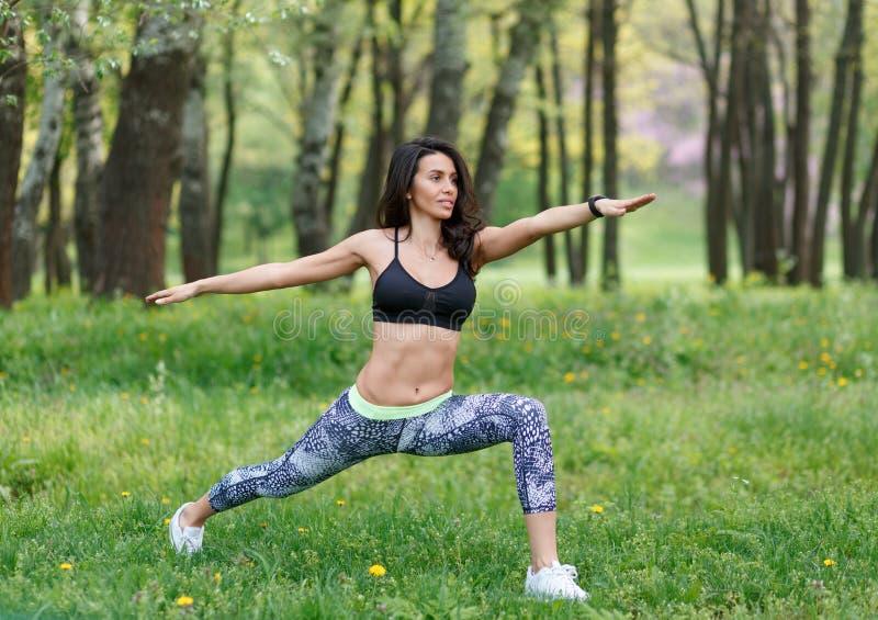 Yoga delgada del entrenamiento de la mujer en parque verde fotos de archivo libres de regalías