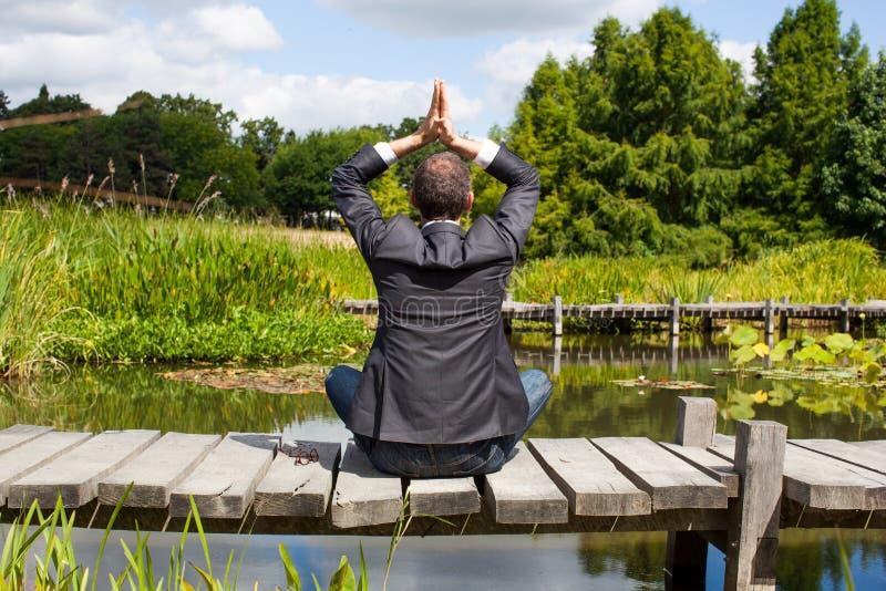Yoga dell'uomo d'affari che prega sul percorso di legno al disopra della superficie fotografie stock