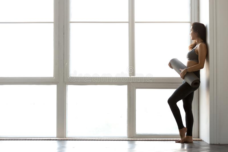 Yoga della tenuta della donna attraente sportiva esile o forma fisica diritta mA immagini stock libere da diritti