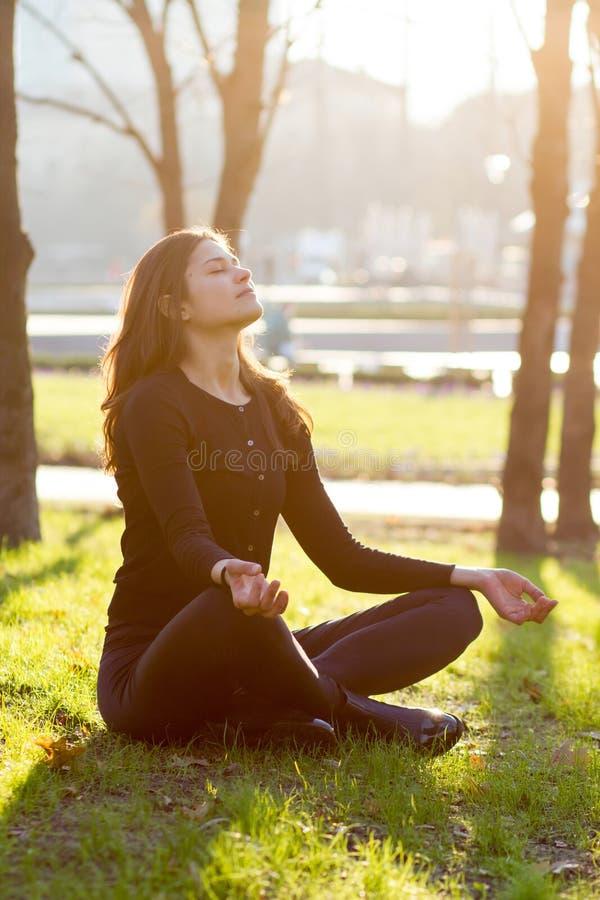 Yoga der jungen Frau, das im Park meditiert stockfoto
