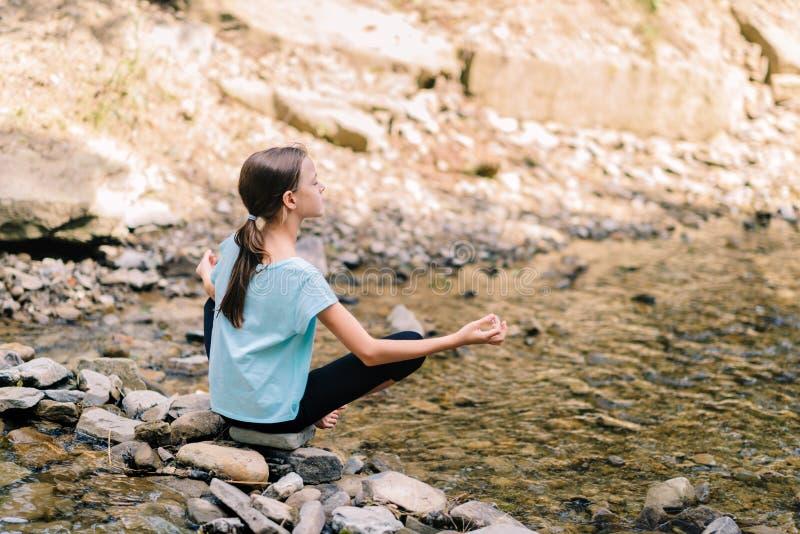 Yoga des jungen Mädchens, das bei dem Sonnenaufgang sitzt auf Steinen auf dem Ufer eines Gebirgsstromes meditiert Jugendmodell, d stockbilder