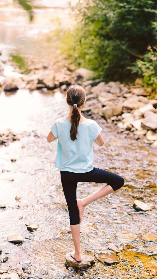 Yoga des jungen Mädchens, das bei dem Sonnenaufgang sitzt auf Steinen auf dem Ufer eines Gebirgsstromes meditiert Jugendmodell, d stockfotografie
