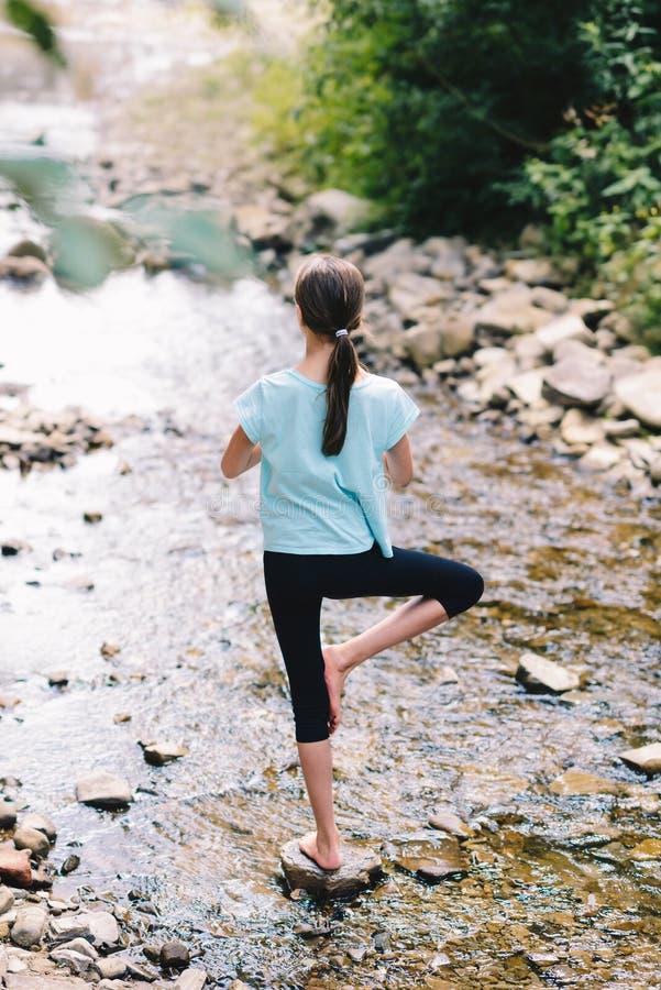 Yoga des jungen Mädchens, das bei dem Sonnenaufgang steht auf Steinen auf dem Ufer eines Gebirgsstromes meditiert Jugendmodell, d stockbild