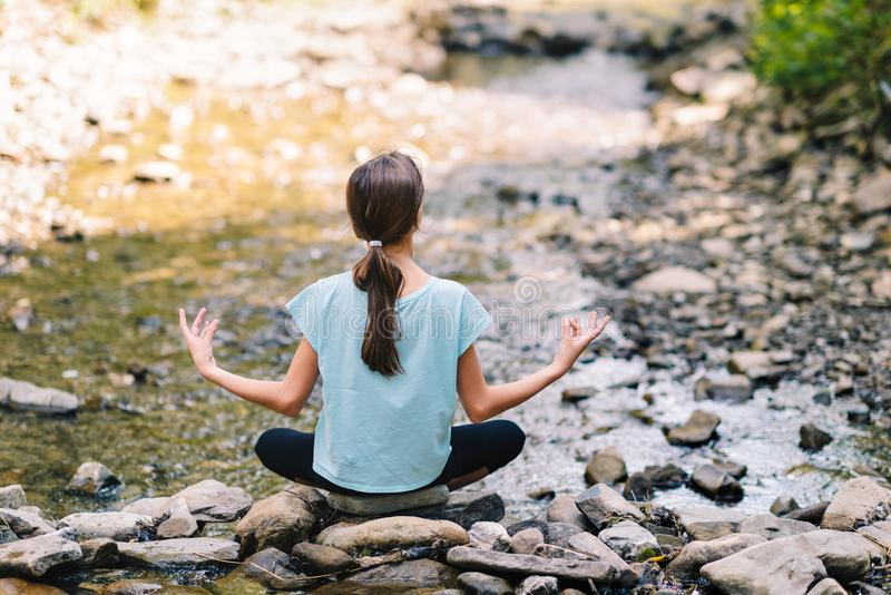 Yoga des jungen Mädchens, das bei Sonnenaufgang auf dem Ufer eines Gebirgsstromes meditiert Jugendmodell, das in der ruhigen Harm stockfoto