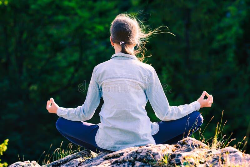 Yoga des jungen Mädchens meditiert bei dem Sonnenuntergang, der auf einem Felsen in den Bergen im Lotussitz sitzt lizenzfreie stockbilder