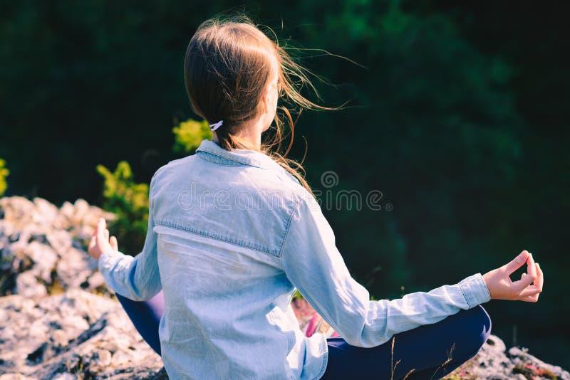 Yoga des jungen Mädchens meditiert bei dem Sonnenuntergang, der auf einem Felsen in den Bergen im Lotussitz sitzt stockfoto