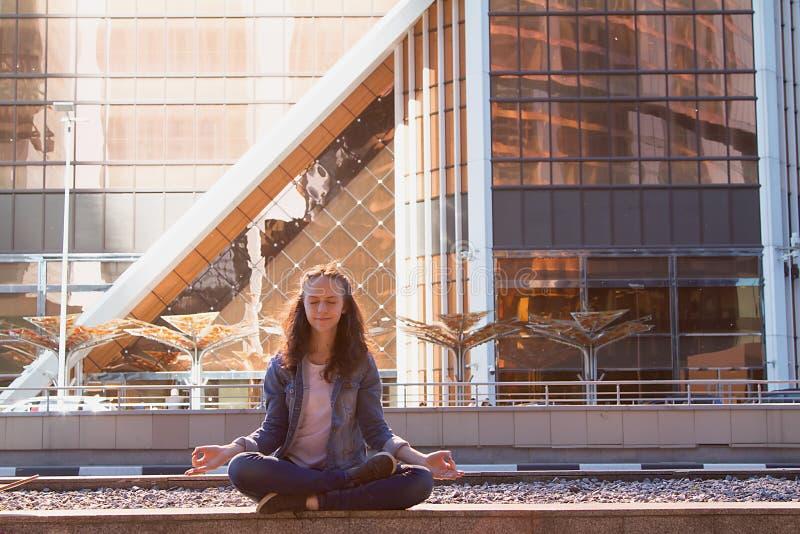 Yoga des jungen Mädchens und meditiert im Lotussitz in einer Großstadt lizenzfreies stockfoto