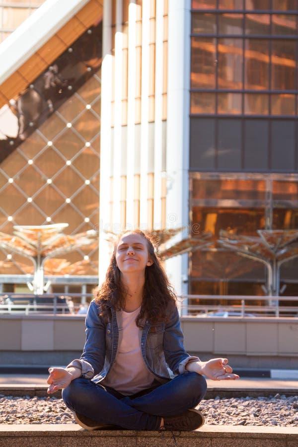 Yoga des jungen Mädchens und meditiert im Lotussitz in einer Großstadt lizenzfreies stockbild