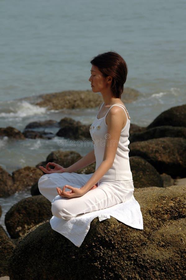 Yoga di Ananda sulla roccia immagine stock
