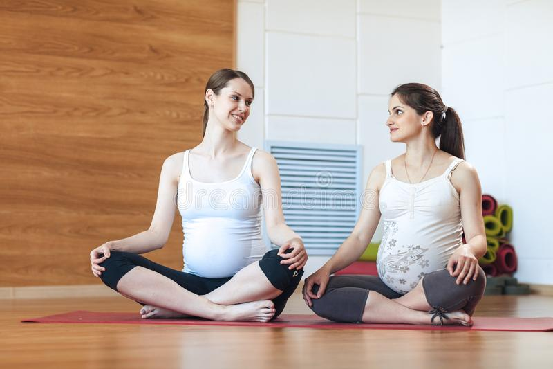 Yoga di gravidanza, concetto di forma fisica Risolvere incinto di due bello giovane modelli di yoga dell'interno Sitti sorridente fotografie stock libere da diritti