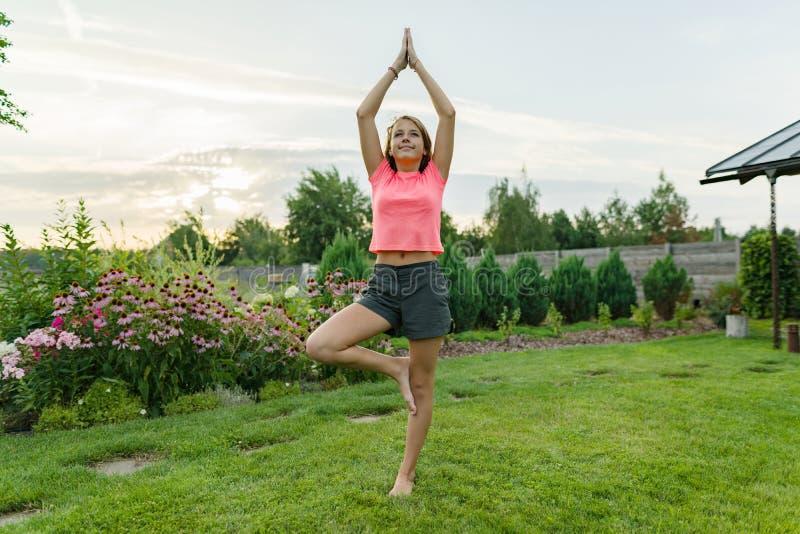 Yoga di pratica del giovane adolescente, meditante su fondo di tramonto di estate, su erba verde, prato inglese vicino alla casa immagini stock