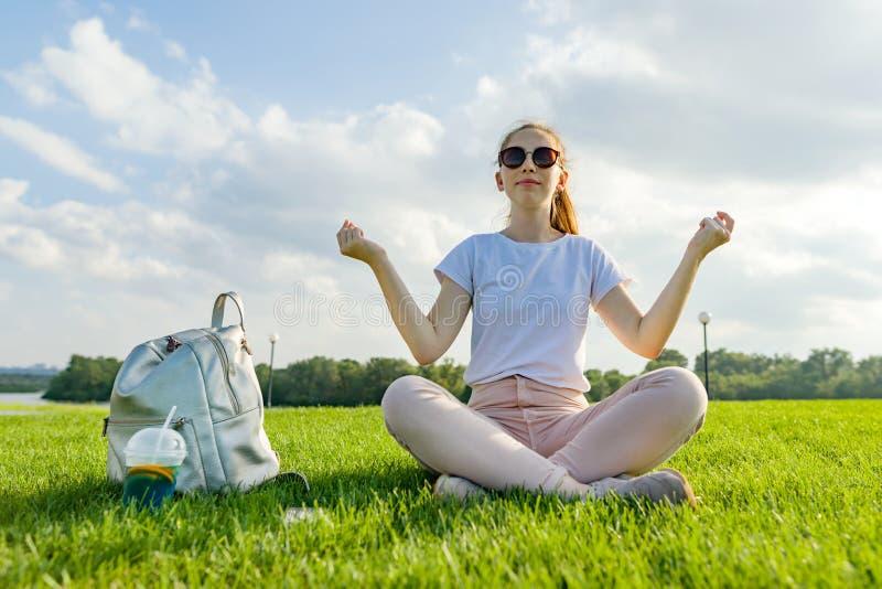 Yoga di pratica del giovane adolescente sull'erba in parco, meditante fotografia stock libera da diritti