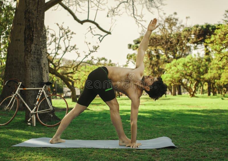 Yoga di pratica dell'uomo nel parco fotografie stock libere da diritti