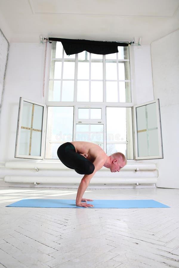 Yoga di pratica dell'uomo sportivo Verticale Urdhva Kukkutasana Gallo ascendente immagine stock